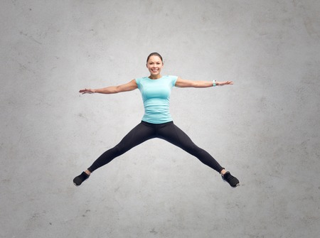 happy smiling sporty young woman jumping in air Stock Photo