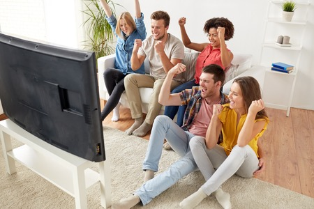 happy friends with remote watching tv at home