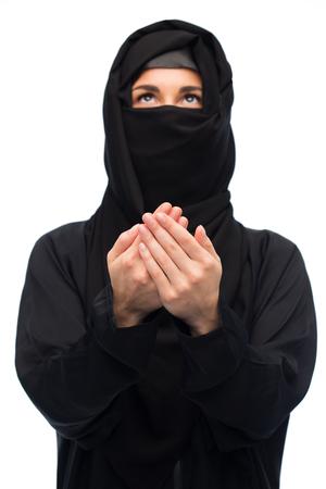 yashmak: praying muslim woman in hijab over white Stock Photo