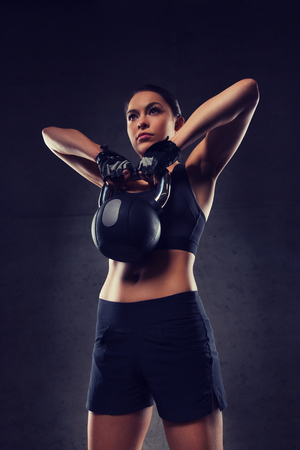 fitness gym: fitness, sport, exercising, weightlifting and people concept - young woman flexing muscles with kettlebell in gym