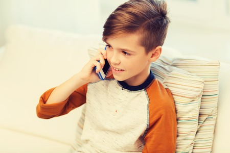 niños platicando: leisure, children, technology, communication and people concept - smiling boy calling on smartphone at home