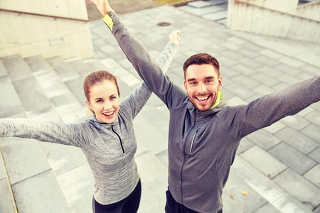 sport fitness: fitness, sport, people and lifestyle concept - happy smiling couple outdoors on city street Stock Photo