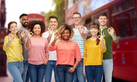 buss: international group of people showing ok in london