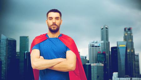 都市の背景に赤いスーパー ヒーロー マントの男