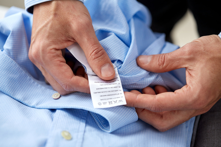 clothes, housework, laundry and people - male hands holding shirt and label with washing instruction Stok Fotoğraf