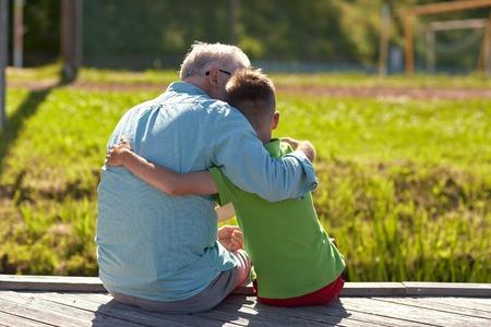 Grootvader en kleinzoon knuffelen op de ligplaats Stockfoto - 74023166