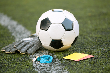 ball, gloves, whistle and cards on soccer field Stock Photo