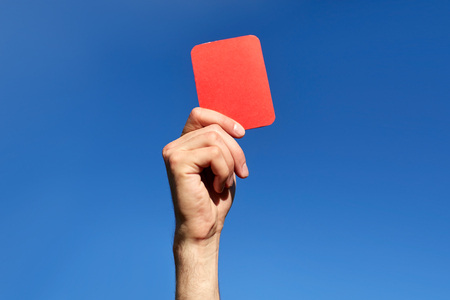 games hand: referee hands with red card on football field