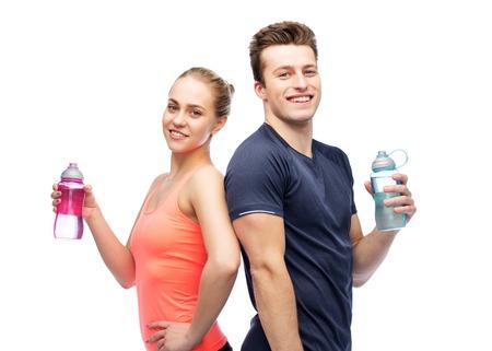 Sportieve man en vrouw met waterflessen