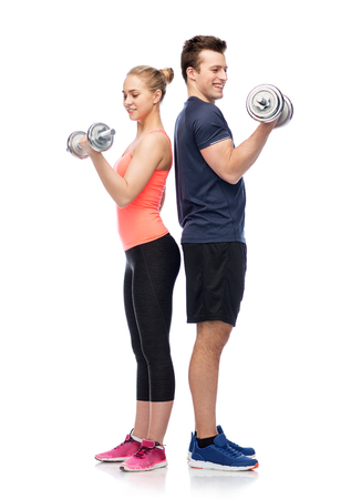 sportive man and woman with dumbbells Фото со стока