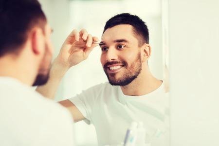 tweezing: man with tweezers tweezing eyebrow at bathroom Stock Photo