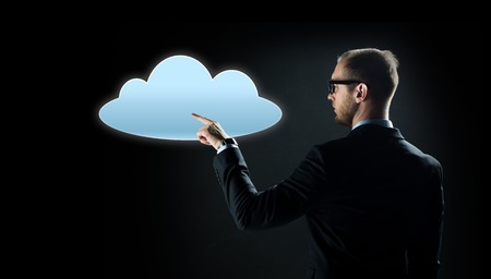 business, virtual reality, future technology, cyberspace and people - businessman in suit and glasses pointing finger to cloud projection over black background