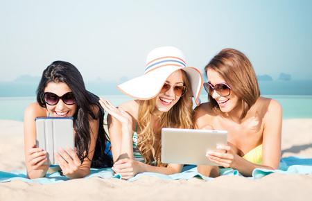 over the edge: summer holidays, technology, people, travel and internet concept - happy young women in bikinis with tablet pc computers sunbathing over infinity edge pool background Stock Photo