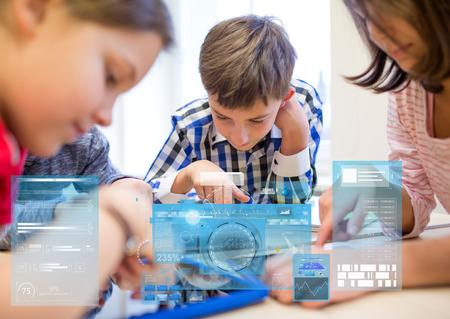 Onderwijs, basisschool, leer, technologie en mensenconcept - groep kinderen met tablet pc computers in de klas over virtuele schermen projecties