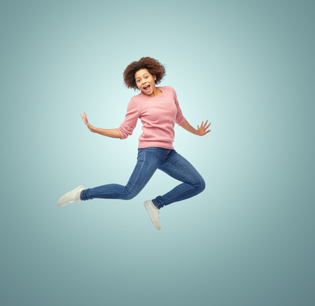 people in action: people, motion and action concept - happy african american young woman jumping over blue background