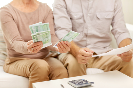 home finances: family, finances savings, old age and people concept - senior couple with papers, money and calculator at home