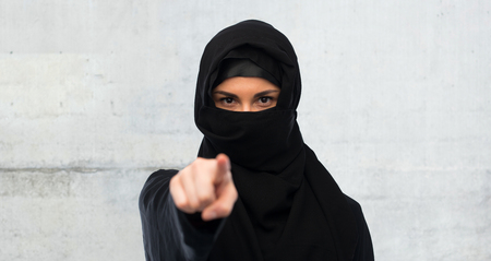 paranja: religious and people concept - muslim woman in hijab pointing finger to you over gray concrete wall background Stock Photo