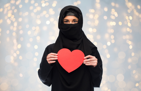 love, charity, valentines day and people concept - muslim woman in hijab holding red heart over holidays lights background