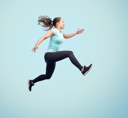 Sport, fitness, motion en mensen concept - gelukkige lachende jonge vrouw springen in de lucht op blauwe achtergrond