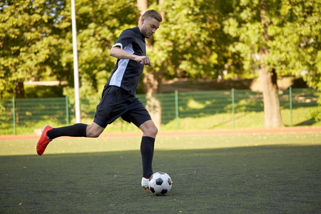 sport, football training and people - soccer player playing with ball on field Imagens