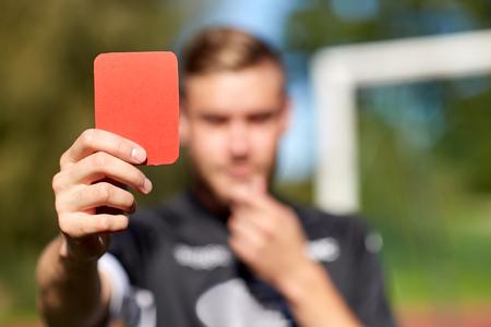sport, voorzichtigheid, spel en mensen - close-up van scheidsrechter handen met fluitje met rode kaart op voetbalveld Stockfoto