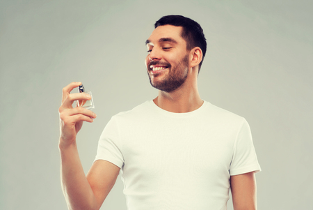 perfumery concept: smiling man with male perfume over gray background
