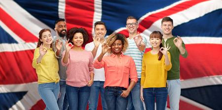 international people showing ok over british flag Stock Photo