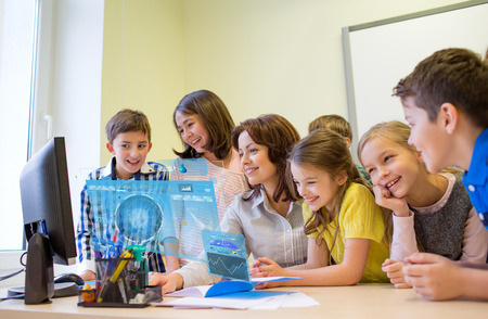group of kids with teacher and computer at school photo
