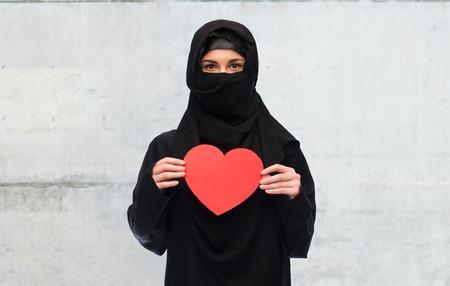 yashmak: muslim woman in hijab holding red heart Stock Photo