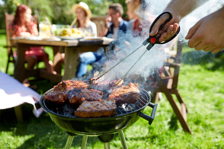 home cooking: man cooking meat on barbecue grill at summer party