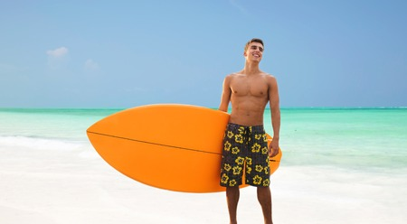 smiling young man with surfboard on beach Stock Photo