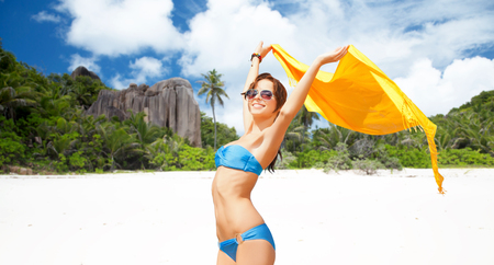woman in bikini and sunglasses with pareo on beach Stock Photo