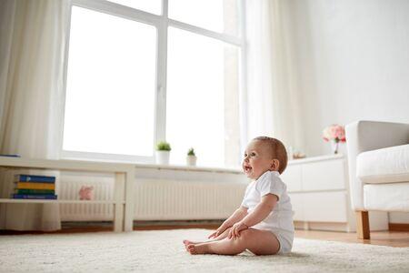 bebe sentado: feliz niño o niña que se sienta en el suelo en casa Foto de archivo