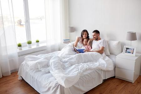 가정에서 침대에서 행복 한 가족 독서 책