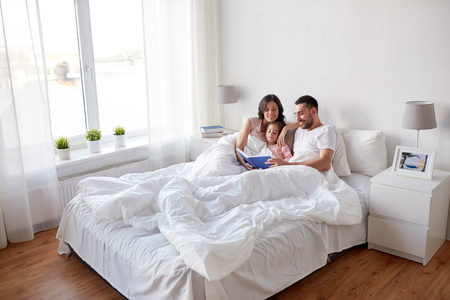 happy family reading book in bed at home Banque d'images