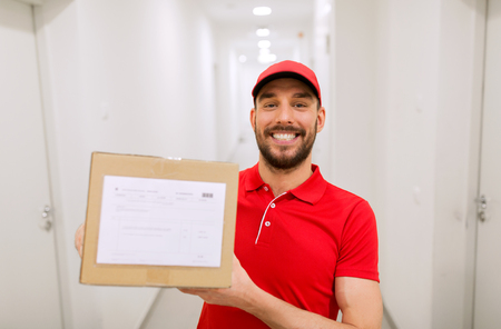 deliverer: delivery man with parcel box in corridor