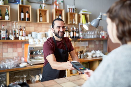business transaction: man or waiter with card reader and customer at bar Stock Photo