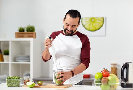 batidos de frutas: Hombre con licuadora cocina alimentos en casa cocina Foto de archivo