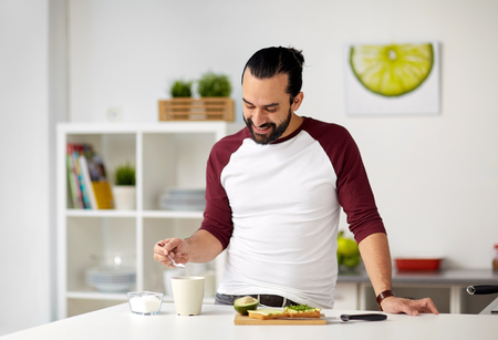 man adding sugar to cup for breakfast at home