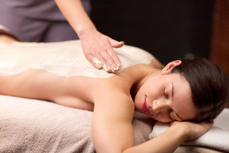 salve: woman lying and having back massage at spa Stock Photo