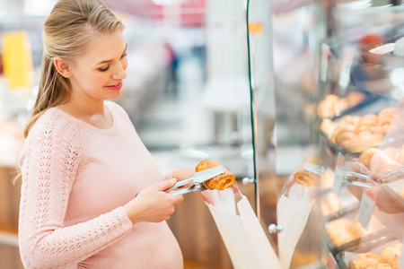 pregnant woman with bag buying buns at grocery
