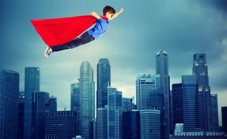街の上を飛んで赤いスーパー ヒーロー マントの少年