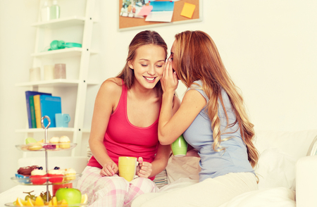 scandalous: young women drinking tea and gossiping at home