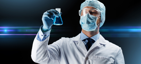 scientist in mask holding flask with chemical