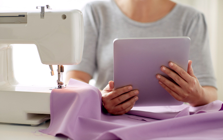 tailor with sewing machine, tablet pc and fabric Imagens