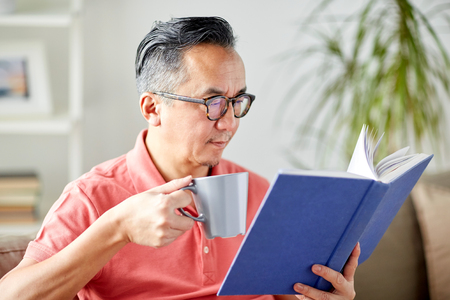 man sitting on sofa and reading book at home Imagens
