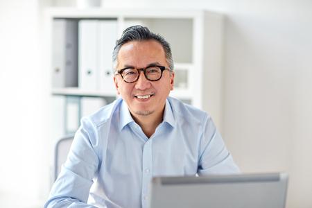 ラップトップのオフィスで眼鏡で幸せなビジネスマン