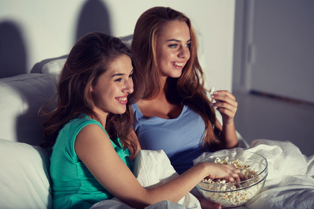 friendship, people, pajama party, entertainment and junk food concept - happy friends or teenage girls eating popcorn and watching movie or tv series at home Imagens