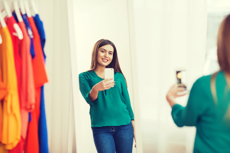 clothing, fashion, style, technology and people concept - happy woman with smartphone taking mirror selfie at home wardrobe Stock Photo