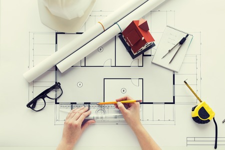 business, architecture, building, construction and people concept - close up of architect hands with ruler and pencil measuring living house blueprint Stock Photo